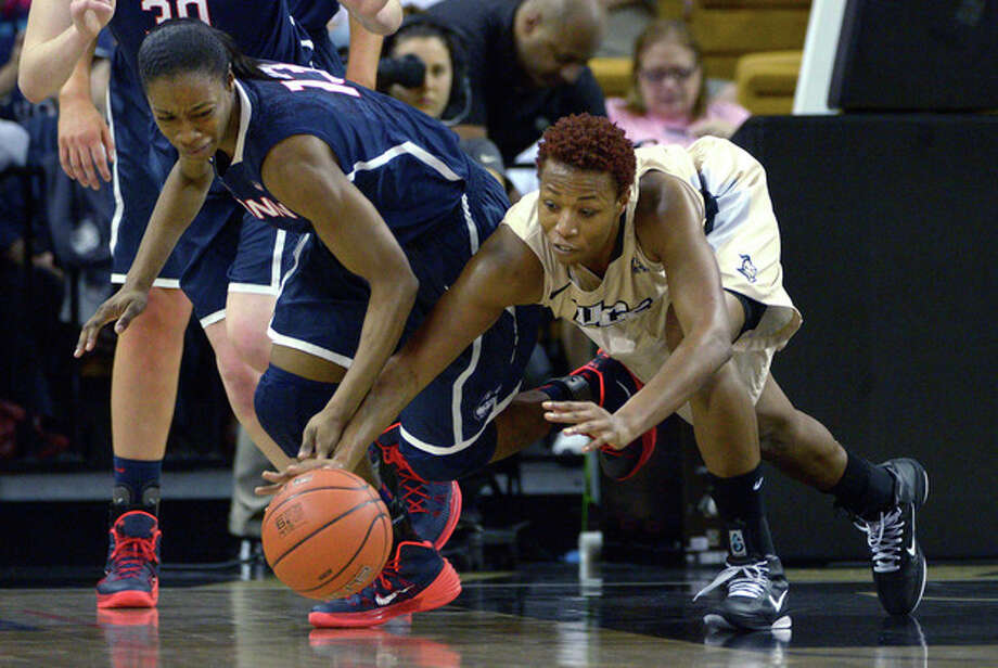 Connecticut guard Brianna Banks (13) and Central Florida's Erika Jones, right, battle for a loose ball during the first half of an NCAA college basketball game in Orlando, Fla., Wednesday, Jan. 1, 2014.(AP Photo/Phelan M. Ebenhack) / FR121174 AP