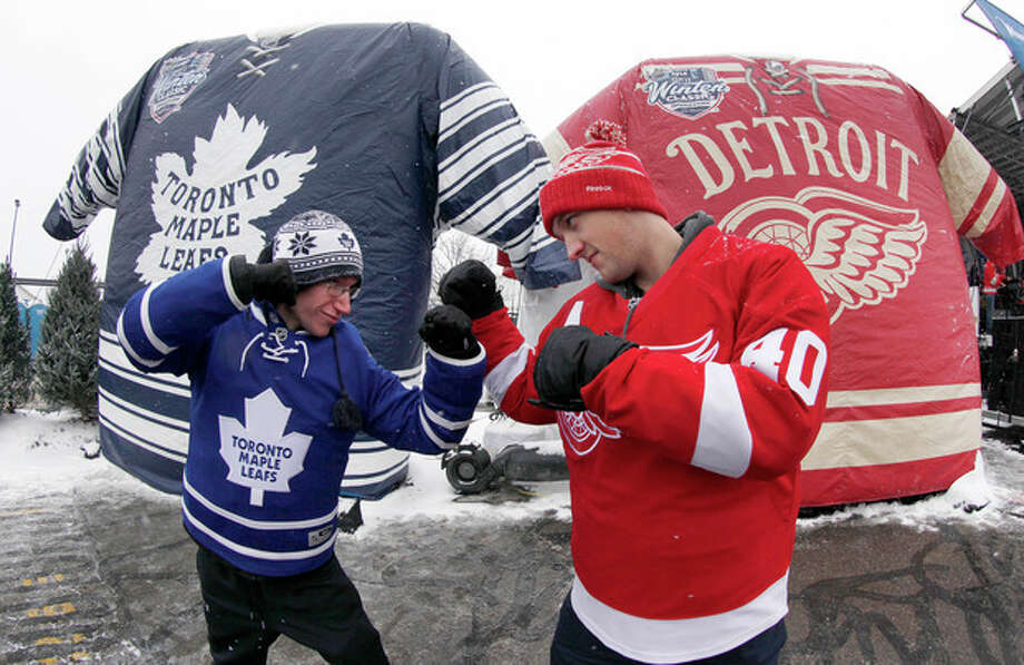 Nathan Dunville, of Halifax, Nova Scotia, left, and Adam Boutilier, of Cole Harbour, Nova Scotia, pose for family photographs at the NHL Winter Classic hockey game at Michigan Stadium in Ann Arbor, Mich., Wednesday, Jan, 1, 2014, where the Detroit Red Wings play the Toronto Maple Leafs. (AP Photo/Paul Sancya) / AP