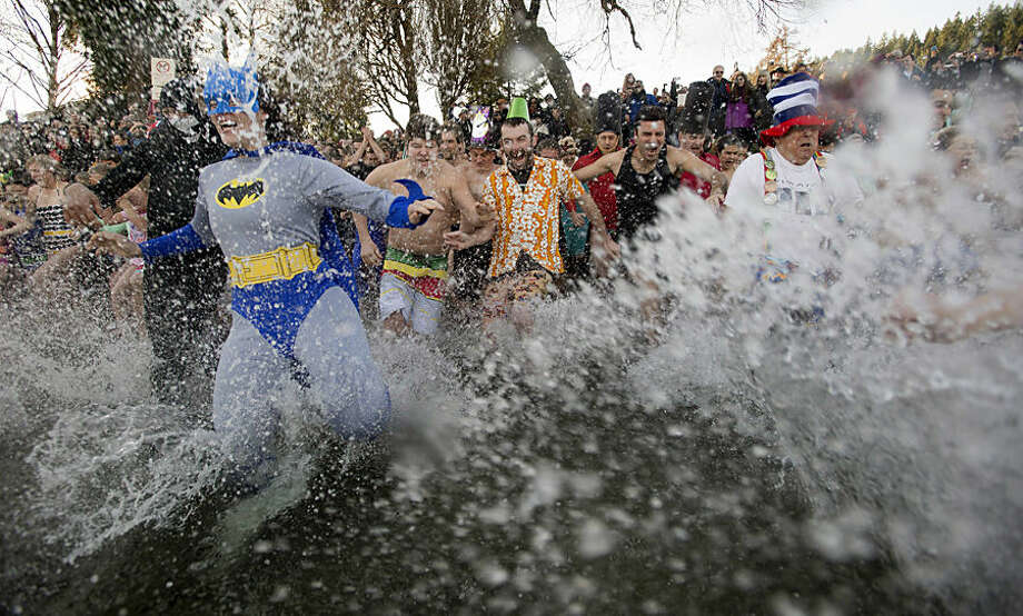 People take part in the annual Penguin Plunge to celebrate the New Year in Deep Cove in North Vancouver, British Columbia, Thursday, Jan. 1, 2015. (AP Photo/The Canadian Press, Jonathan Hayward)