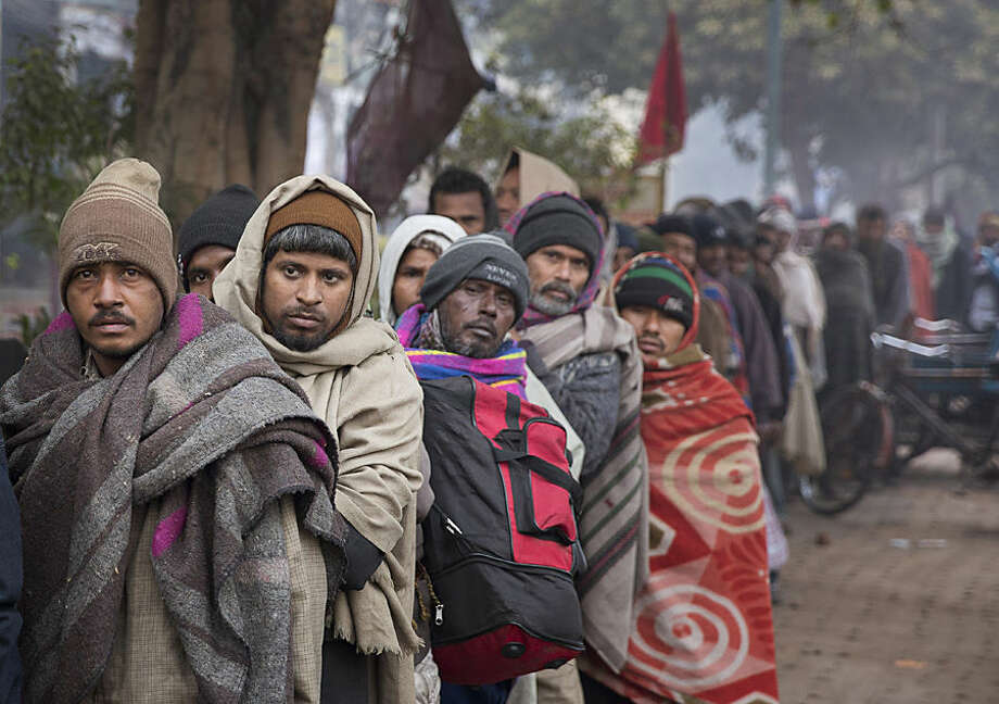 Homeless people wait in a queue for free food distribution on a cold morning in New Delhi, India, Thursday, Jan. 1, 2015. (AP Photo/Manish Swarup)