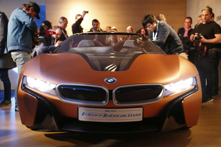 People look at the BMW i Vision Future Interaction concept car during a news conference at CES Press Day at CES International, Tuesday, Jan. 5, 2016, in Las Vegas. (AP Photo/John Locher)