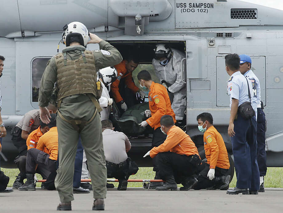 A U.S. Navy helicopter crew member, left, salutes as the U.S. Navy personnel from USS Sampson unload the body of a victim aboard AirAsia Flight 8501 from the helicopter, assisted by Indonesian National Search and Rescue Agency personnel and policemen, upon arrival at the airport in Pangkalan Bun, Indonesia, Friday, Jan. 2, 2015. The investigation into the AirAsia crash has turned to the ocean floor, with more sonar equipment and metal detectors deployed Friday to scour the seabed for wreckage, including the plane's black boxes. (AP Photo/Achmad Ibrahim)