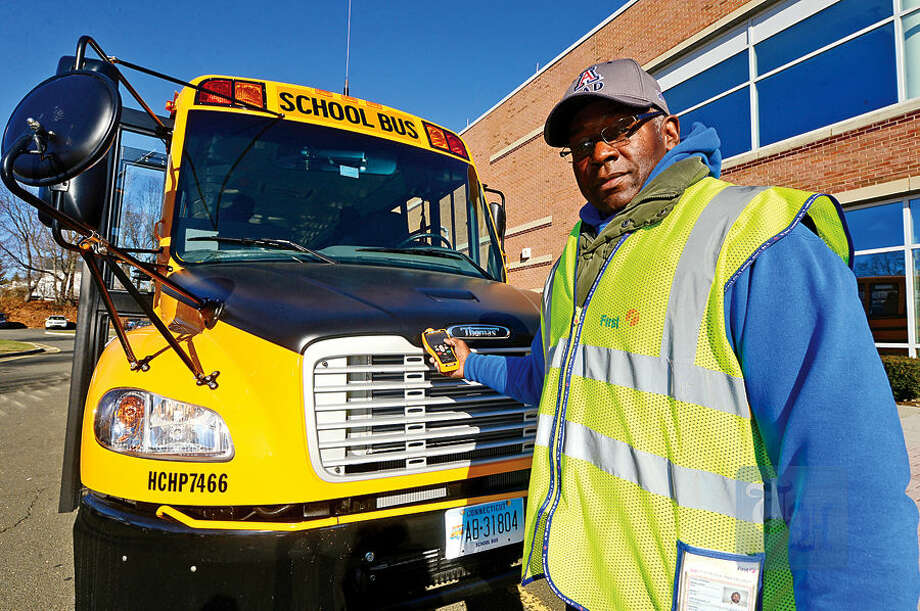 Hour photo / Erik Trautmann First Student driver Kevin Brown demonstrates the improved Zonar safety check system in the new Thomas Built SAF-T-LINER® C2 school buses that will be put into service this week .
