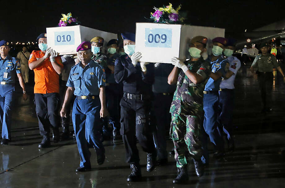 Indonesian military personnel carry coffins containing the bodies of victims of AirAsia Flight 8501 upon arrival at Juanda Naval Airbase in Surabaya, East Java, Indonesia, Friday, Jan. 2, 2015. After nearly a week of searching for the victims of AirAsia Flight 8501, rescue teams battling monsoon rains had their most successful day yet on Friday, more than tripling the number of bodies pulled from the Java Sea, some still strapped to their seats. (AP Photo/Dita Alangkara)
