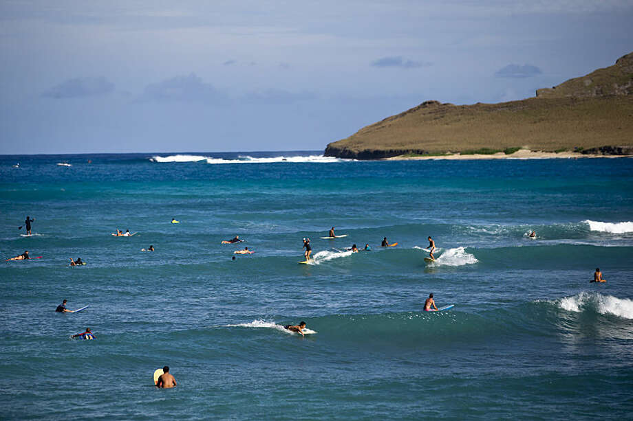 People surf on the waves by Baby Makapuu Beach near where President Barack Obama and the first family are snorkeling at Hanauma Bay Nature Preserve, according to the White House, Thursday, Jan. 1, 2015, on the island of Oahu in Hawaii during the Obama family vacation. (AP Photo/Jacquelyn Martin)