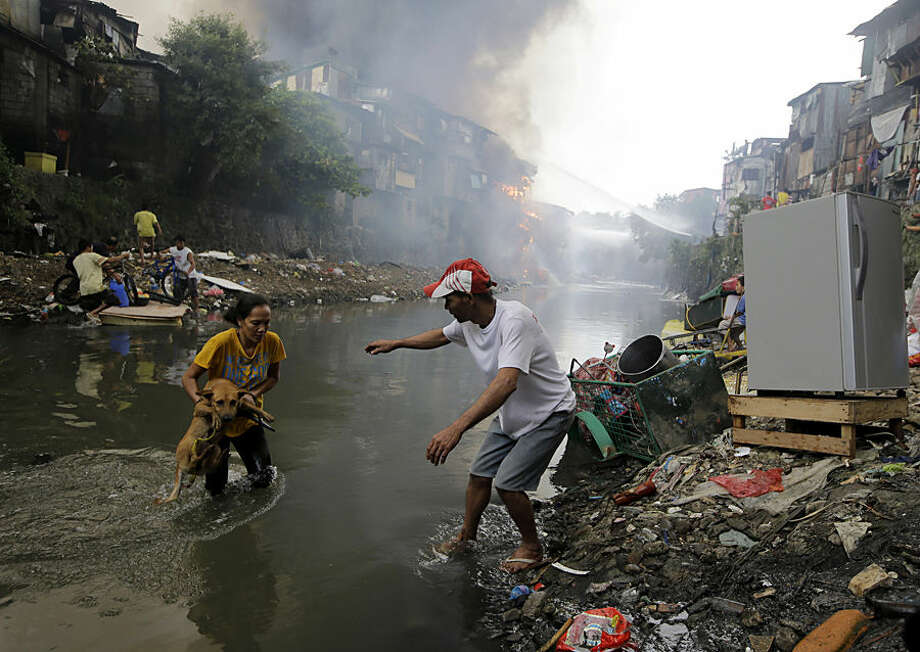 Residents save their pet dog as a huge fire rages along a creek in the suburban Quezon city north of Manila, Philippines, on New Year's day Thursday, Jan. 1, 2015. A huge fire, believed to have been ignited by firecrackers, razed hundreds of shanties in the slum Thursday in one of more than a dozen fires reported across the country as Filipinos welcomed the New Year. (AP Photo/Bullit Marquez)