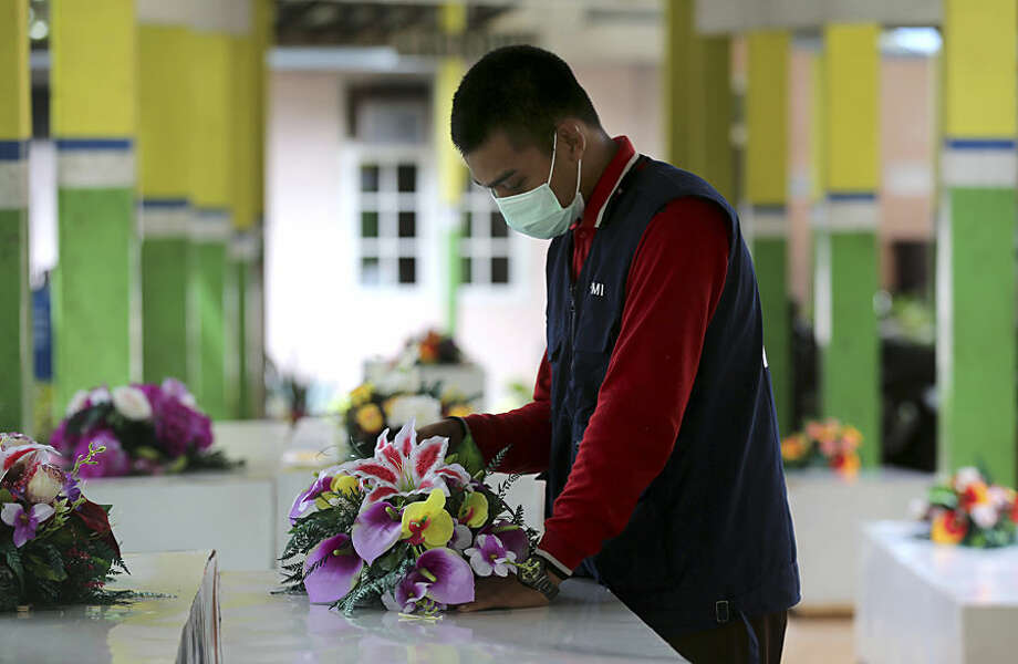 A member of the Indonesia Red Cross prepares coffins for the victims of AirAsia Flight 8501 at the main hospital in Pangkalan Bun, Indonesia, Friday, Jan. 2, 2015. More ships arrived Friday with sensitive equipment to hunt for the fuselage of the flight and the more than 145 people still missing since it crashed into the sea five days ago. (AP Photo/Tatan Syuflana)
