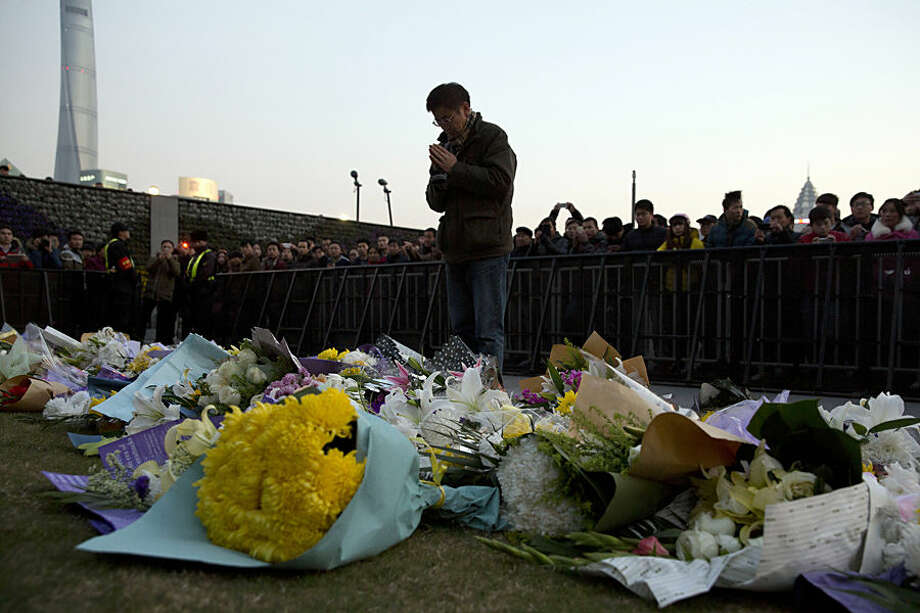A man prays after laying flowers at the site of a deadly stampede in Shanghai, China, Thursday, Jan. 1, 2015. People unable to contact friends and relatives streamed into hospitals Thursday, anxious for information after a stampede during New Year's celebrations in Shanghai's historic waterfront area killed dozens of people in the worst disaster to hit one of China's showcase cities in recent years. (AP Photo/Ng Han Guan)