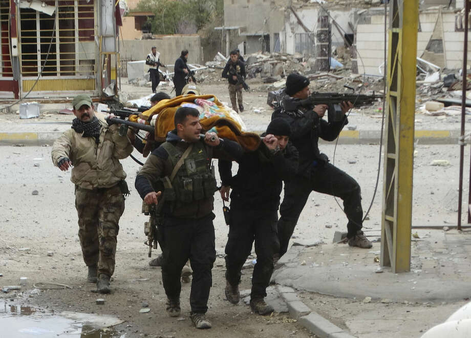 In this Monday, Jan. 4, 2016, photo, Iraqi security forces and allied Sunni tribal fighters evacuate an injured woman after she was shot by Islamic State group fighters as she tried to cross from neighborhoods under control of Islamic State group to neighborhoods under control of Iraqi security forces in Ramadi, 70 miles (115 kilometers) west of Baghdad, Iraq. Islamic State extremists had captured Ramadi in May, in one of its biggest advances since the U.S.-led coalition began striking the group in 2014. Recapturing the city, which is the provincial capital of Anbar, provided a major morale boost for Iraqi forces. (AP Photo)