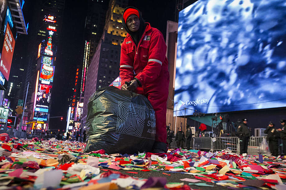 A sanitation worker begins cleaning Times Square after a New Years Eve celebration, Thursday, Jan. 1, 2015, in New York. Thousands braved the cold to watch the annual ball drop and ring in the new year. (AP Photo/John Minchillo)