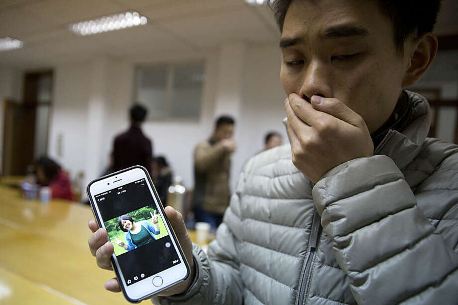 A man who only gave his surname Zhao shows a photo of his girlfriend Pan Haiqin who was killed in the deadly stampede in Shanghai, China, Friday, Jan. 2, 2015. People unable to contact friends and relatives streamed into hospitals Thursday, anxious for information after a stampede during New Year's celebrations in Shanghai's historic waterfront area killed 36 people in the worst disaster to hit one of China's showcase cities in recent years. (AP Photo/Ng Han Guan)