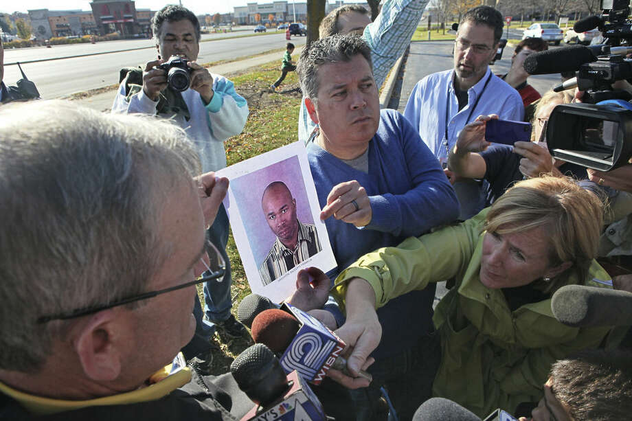 FILE - In this Oct. 21, 2012 file photo, Brookfield police Lt. Mark Millard, left, holds a photo of shooting suspect Radcliffe Franklin Haughton, as he answers questions at a news conference near the shooting site in Brookfield, Wis. President Barack Obama's moves to license more private gun sellers and do background checks on buyers will have the greatest impact on the fast-growing and largely unregulated world of online sales. But it's not clear that the steps will transform the broader gun market, and even the White House says it can't predict how much good it will do. Online transactions have included weapons later used in high-profile mass shootings, including the 2012 mass shooting in Brookfield, Wisconsin. (Milwaukee Journal-Sentinel, Michael Sears via AP, File) MAGS OUT; ONLINE OUT