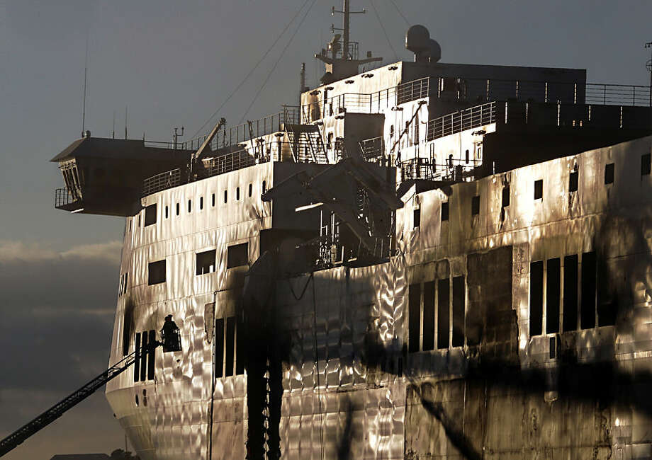 A fireman works outside the Norman Atlantic ferry after that has been towed into the port of Brindisi, southern Italy, Friday, Jan. 2, 2015. The blaze that broke out Sunday and torched the ferry has killed at least 11 people and authorities prepared to search it for possible more dead. Italy says 477 people were rescued, most by helicopters that plucked survivors off the top deck in gale-force winds and carried them to nearby boats. (AP Photo/Antonio Calanni)