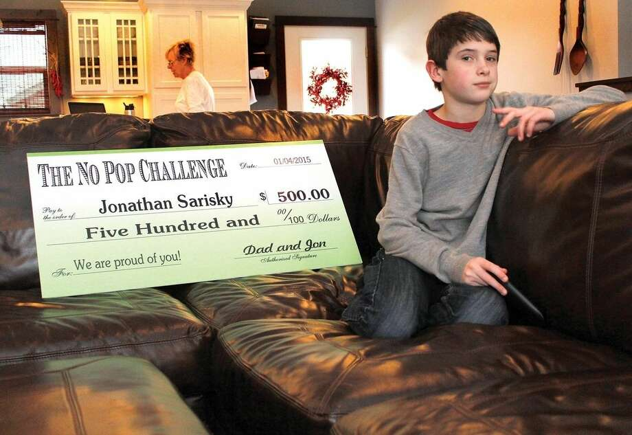 "Jonathan Sarisky, 11, poses Dec. 24, 2014, in Livingston, Mont., with the big check he received from his parents for successfully completing the ""No Pop Challenge,"" in which Jon, as he likes to be called, avoided all sugary beverages for one year. Per the contract detailing the terms of the challenge, Jonathan is free to spend the $500 however he chooses. (AP Photo/Livingston Enterprise, Hunter D'Antuono)"