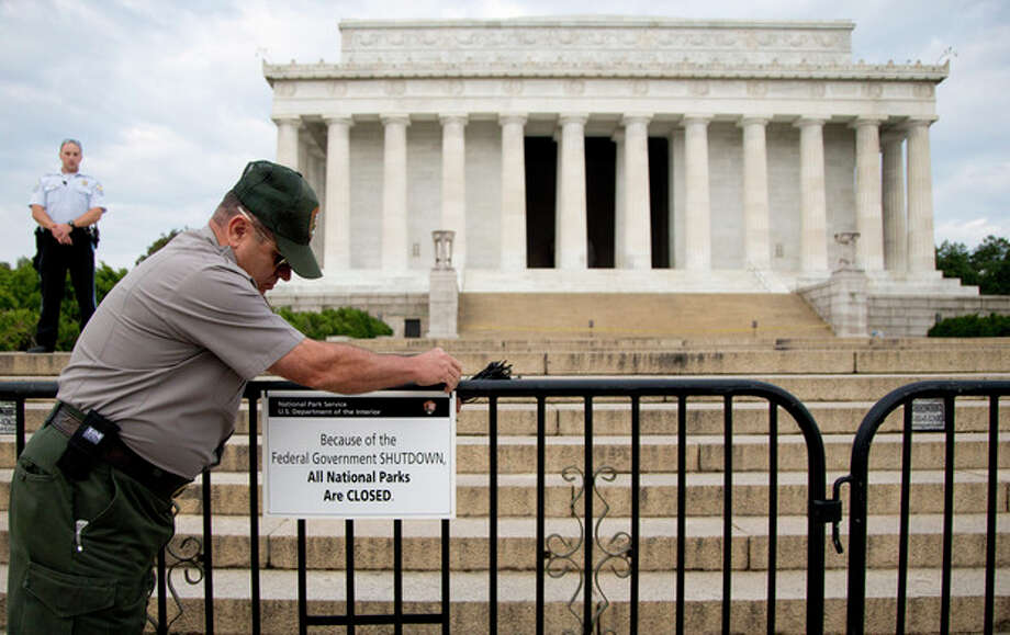 FILE - This Oct. 1, 2013 file photo shows a US Park Police officer watching at left as a National Park Service employee posts a sign on a barricade closing access to the Lincoln Memorial in Washington. About half of Americans expect 2014 to be a better year than 2013, according to the recent AP-Times Square New Year's Eve poll, and judging by the standard questions pollsters use to measure the public mood, it doesn't seem like it could be much worse. (AP Photo/Carolyn Kaster, File) / AP