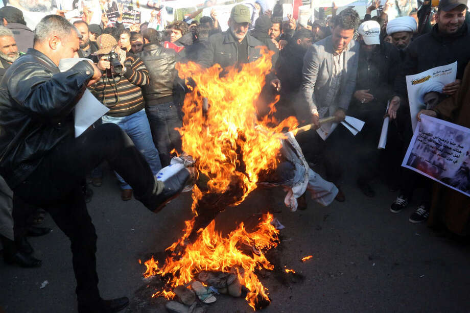 Followers of Shiite cleric Muqtada al-Sadr burn an effigy of King Salman of Saudi Arabia as they hold posters of Sheik Nimr al-Nimr during a demonstration in Baghdad, Iraq, Monday, Jan. 4, 2016. Demonstrations are also being called for in the predominantly Shiite southern cities of Najaf and Basra, after Saudi Arabia executed a prominent opposition Shiite cleric convicted of terrorism charges, sparking anger in Iran and among Shiites across the region. (AP Photo/Khalid Mohammed)