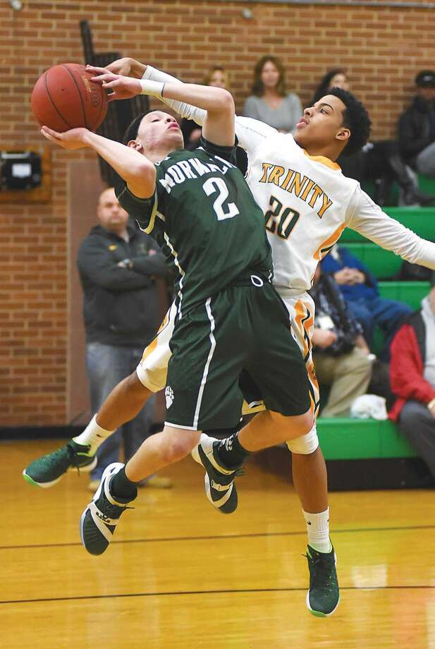 Hour photo/John Nash - Norwalk's Mark Crafter Jr. (2) gets fouled by Trinity Catholic's Cameron Blake during the first half of Tuesday's FCIAC boys basketball game at Walsh Court in Stamford.