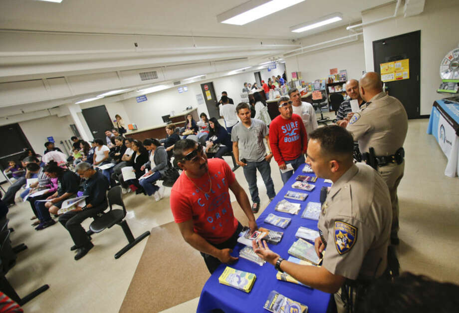 FILE - In this April 23, 2014, file photo, California Highway Patrol officers Armando Garcia, right, and Ray Patton explain to immigrants the process of getting a drivers license during an information session at the Mexican Consulate, in San Diego. California is gearing up to start issuing driver's licenses to immigrants in the country illegally in a bid to make the roads safer that could also give more than a million people access to state-issued identification. (AP Photo/Lenny Ignelzi, File)