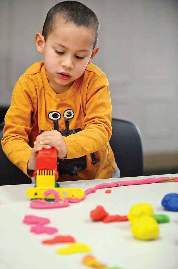 Hour photo / Erik Trautmann Sebastian Mesa, 3, squeezes out Play-Doh during the Play-Doh Palooza at the a SoNo Branch Library Friday. The activity was a SoNo Branch Library Kids Build Program to help foster creativity.