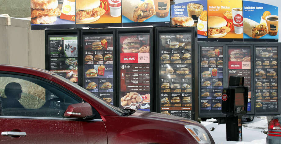 FILE - In this Jan. 26, 2009, file photo, a customer looks at the menu at a McDonald's drive-thru in Williamsville, N.Y. As people express distaste for food they think is overly processed, chains including McDonald's and Taco Bell are trying to shed their reputation for serving reheated meals that are kept intact with chemicals. (AP Photo/David Duprey, File)