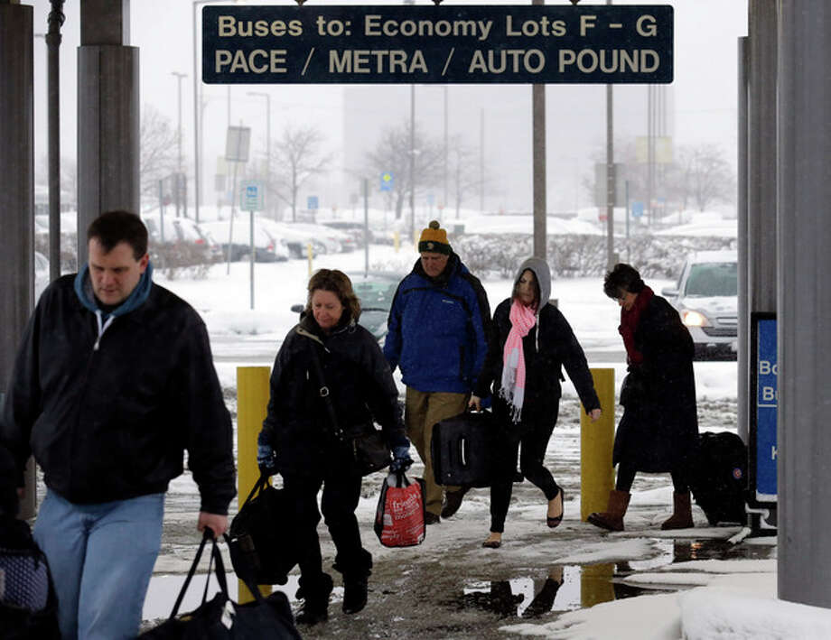 Travelers walk a train station in the economic parking lot at O'Hare International Airport in Chicago, Thursday, Jan. 2, 2014. Another one to three inches of snow could fall across the Chicago metro area Thursday with even more falling in the southern part of the region, according to the National Weather Service. (AP Photo/Nam Y. Huh) / AP