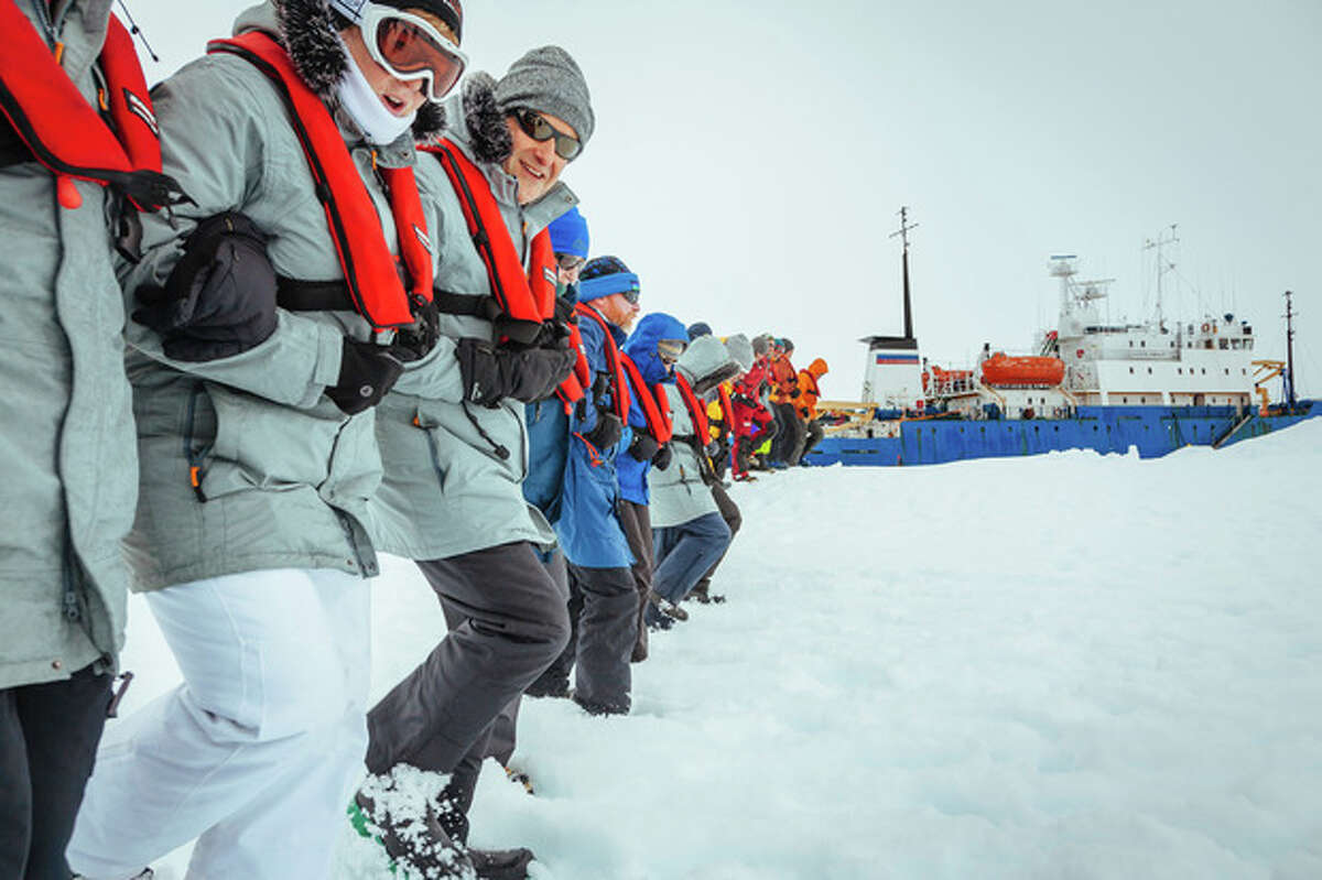In this Tuesday, Dec. 31, 2013 image provided by Australasian Antarctic Expedition/Footloose Fotography, passengers from the Russian ship MV Akademik Shokalskiy link arms and stamp out a helicopter landing site on the ice near the trapped ship 1,500 nautical miles south of Hobart, Australia. Passengers on board a research ship that has been trapped in Antarctic ice for a week are expected to be rescued by helicopter, after three icebreakers failed to reach the paralyzed vessel, officials said Tuesday. (AP Photo/Australasian Antarctic Expedition/Footloose Fotography, Andrew Peacock) EDITORIAL USE ONLY