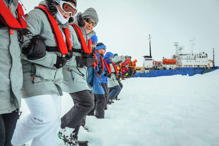 In this Tuesday, Dec. 31, 2013 image provided by Australasian Antarctic Expedition/Footloose Fotography, passengers from the Russian ship MV Akademik Shokalskiy link arms and stamp out a helicopter landing site on the ice near the trapped ship 1,500 nautical miles south of Hobart, Australia. Passengers on board a research ship that has been trapped in Antarctic ice for a week are expected to be rescued by helicopter, after three icebreakers failed to reach the paralyzed vessel, officials said Tuesday. (AP Photo/Australasian Antarctic Expedition/Footloose Fotography, Andrew Peacock) EDITORIAL USE ONLY / AustraAustralasian Antarctic Expedition/Footloose Fotography