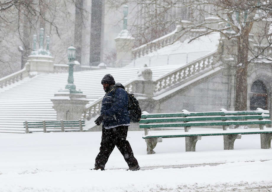 A pedestrian walks through the snow outside the state Capitol on Thursday, Jan. 2, 2014, in Albany, N.Y. Up to 5 inches of snow have fallen in eastern New York early Thursday, but the National Weather Service said some areas from Buffalo to Albany could get up to 12 inches by the time the storm subsides on Friday. (AP Photo/Mike Groll) / AP
