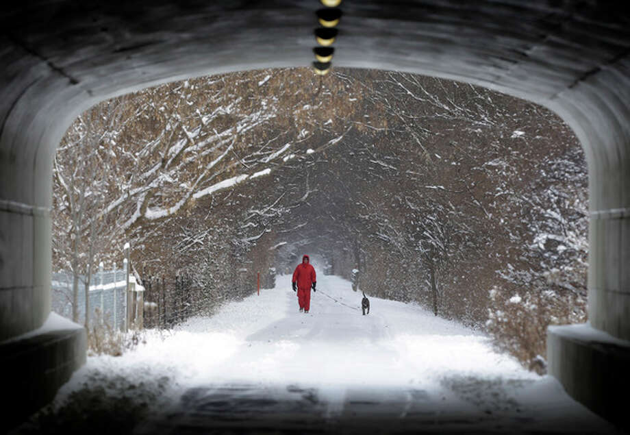 Naoom Haimson walks his dog, Molly, on the snow covered Monon Trail in Carmel, Ind., Thursday, Jan. 2, 2014. Over 5 inches of snow fell in Central Indiana. (AP Photo/Michael Conroy) / AP