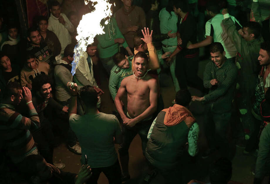 "In this Thursday, Dec. 19, 2013 photo, Egyptian youths dance, to ""Mahraganat,"" Arabic for ""festivals,"" music, a rapid-fire electronic beat, mixed with hypnotic rhythms, during a bachelors party, in El-Marg, a suburb northeast of Cairo, Egypt. Mahraganat singers emerged before the 2011 revolution, but the trend has spread rapidly because of the loosening of societal restrictions attributed at least in part to the uprising. (AP Photo/Nariman El-Mofty) / AP"