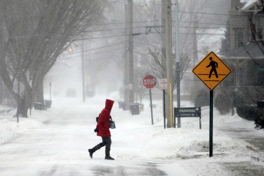A woman crosses North Summit Street, Thursday, Jan. 2, 2014, on her way to the Wood County Courthouse in Bowling Green, Ohio. A winter weather advisory is in effect for the area. (AP Photo/Sentinel-Tribune, J.D. Pooley) MANDATORY CREDIT, TOLEDO BLADE OUT / Sentinel-Tribune
