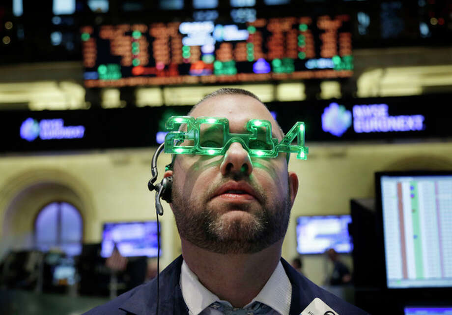 FILE - In this Tuesday, Dec. 31, 2013, file photo, a trader wears glasses celebrating the new year while working on the floor at the New York Stock Exchange in New York. U.S. stock futures are under pressure Jan. 2, 2014, after markets in 2013 saw their biggest gains in nearly two decades. (AP Photo/Seth Wenig, File) / AP