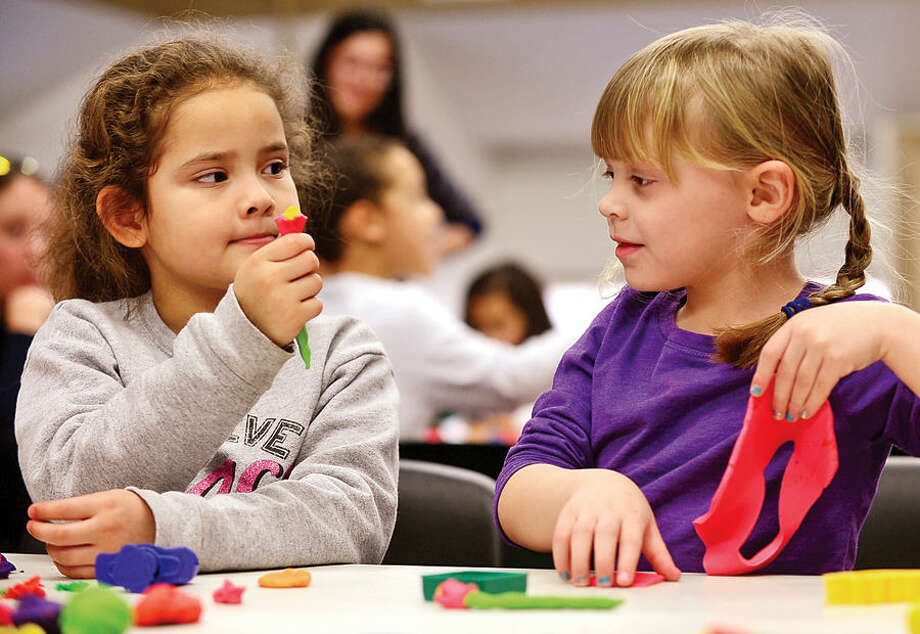 Hour photo / Erik Trautmann Faith Supple, 6, and Miley Senft, 4, share their Play-Doh creations during Play-Doh Palooza at the a SoNo Branch Library Friday. The activity was a SoNo Branch Library Kids Build Program to help foster creativity.