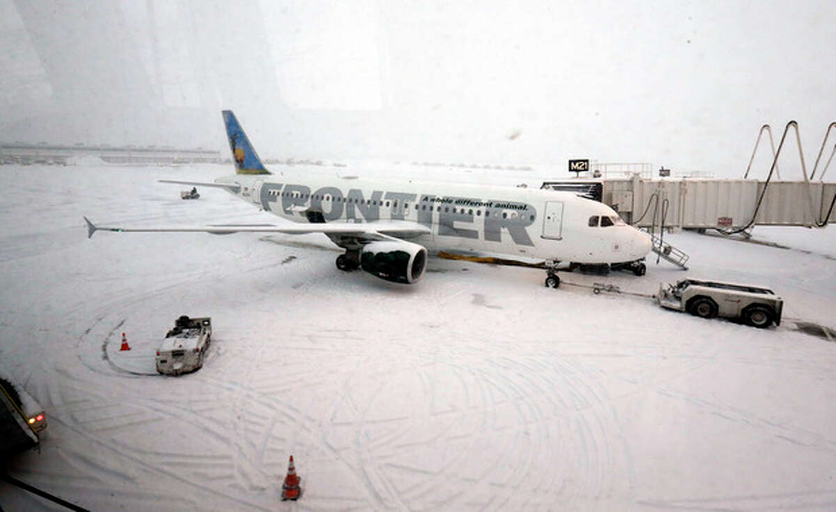 A Frontier airplane waits for passengers at O'Hare International Airport in Chicago, Thursday, Jan. 2, 2014. Another one to three inches of snow could fall across the Chicago metro area Thursday with even more falling in the southern part of the region, according to the National Weather Service. (AP Photo/Nam Y. Huh)