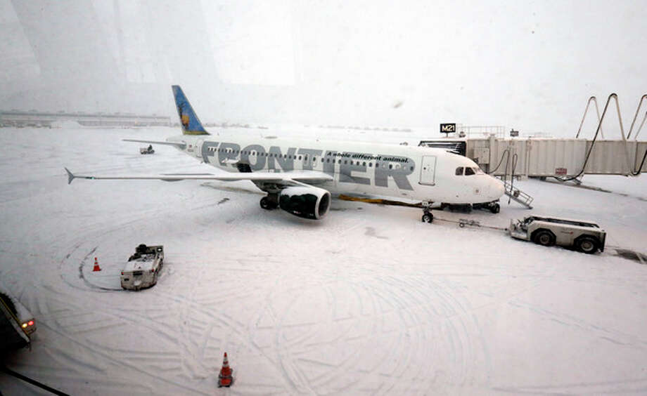A Frontier airplane waits for passengers at O'Hare International Airport in Chicago, Thursday, Jan. 2, 2014. Another one to three inches of snow could fall across the Chicago metro area Thursday with even more falling in the southern part of the region, according to the National Weather Service. (AP Photo/Nam Y. Huh) / AP
