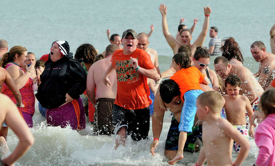 People react to the cold water during the Ocean Lakes 13th annual Polar Bear Plunge at Ocean Lakes Family Campground, in Myrtle Beach, S.C., on Tuesday, Dec. 31, 2013. Each person donated a nonperishable food item that will go to local food banks. (AP Photo/The Sun News, Charles Slate) / The Sun News