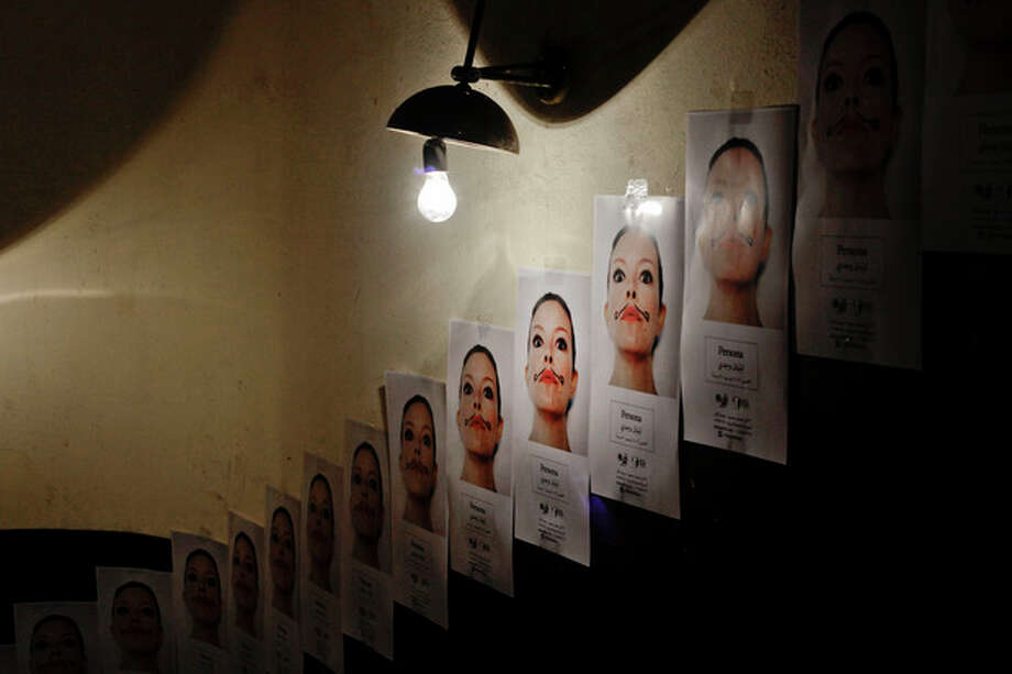 "This Saturday, Dec. 14, 2013 photo, shows posters taped to a wall for an art exhibition entitled ""Persona"" by photographer artist Lilian Wagdy inside a building, near Tahrir Square, Cairo. Egypt's dizzying ride over the past three years since the toppling of autocratic Hosni Mubarak has revolutionized its pop culture scene, from language to music and art, bringing in a vibe of rebellion and voices from youths. Wagdy asked women to choose characters they idolized and wanted to portray to reveal parts of their hidden personalities. The women posed for Wagdy unveiling their inner identity. (AP Photo/Nariman El-Mofty) / AP"