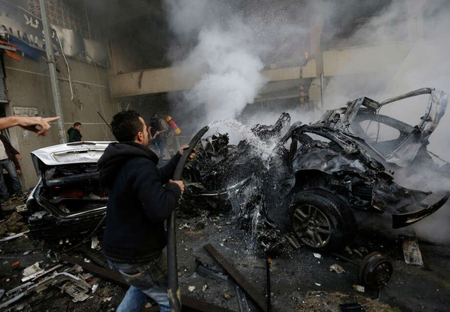 A Lebanese man extinguishes burned cars at the site of a car bomb explosion in a stronghold of the Shiite Hezbollah group at the southern suburb of Beirut, Lebanon, Thursday, Jan. 2, 2014. A large explosion took place during rush hour in the Haret Hreik neighborhood. (AP Photo/Hussein Malla) / AP