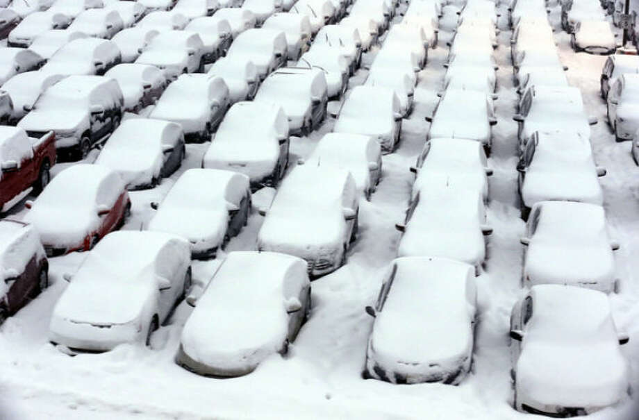 Cars are covered by snow in rental car parking lot at O'Hare International Airport in Chicago, Thursday, Jan. 2, 2014. Another one to three inches of snow could fall across the Chicago metro area today with even more falling in the southern part of the region, according to the National Weather Service. (AP Photo/Nam Y. Huh)