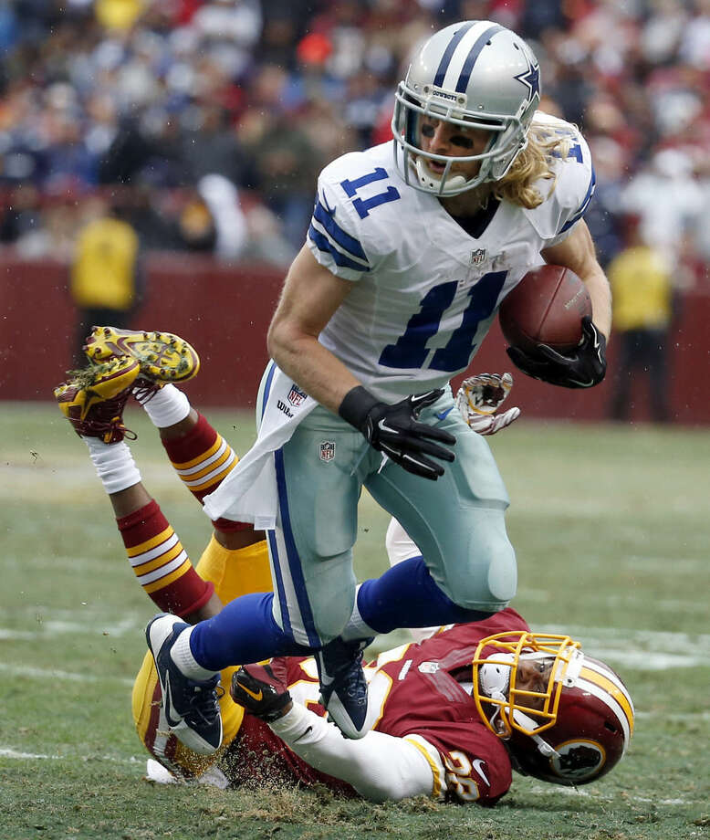 FILE - In this Dec. 28, 2014, file photo, Dallas Cowboys wide receiver Cole Beasley (11) breaks a tackle by Washington Redskins cornerback Justin Rogers during the second half of an NFL football game in Landover, Md. While quarterbacks and other big-name, high-salaried players get most of the attention, unlikely heroes often emerge in the playoffs to help their team win. Philly Brown, Josh Harris and Cole Beasley are among the lesser-known players who could step up this wild-card weekend. (AP Photo/Alex Brandon, File)