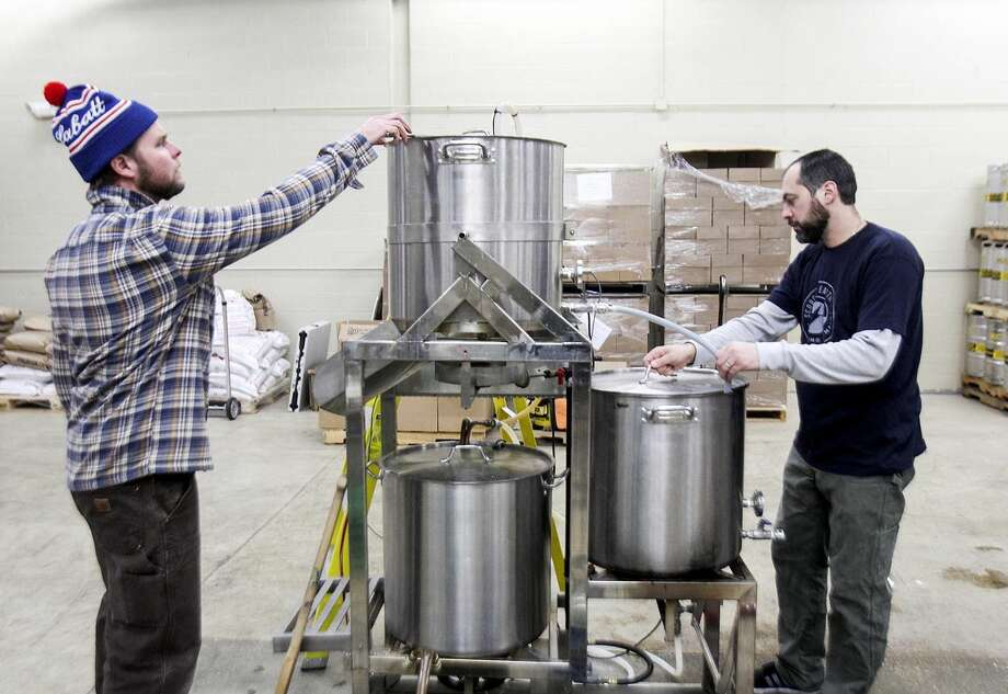 AP photo/Northwest Herald, Sarah Nader In this Wednesday, Dec. 10, 2014 photo, Dan Payson, head brewer, left, and Mark Gres, production assistant, extract sugar from malted barley while brewing a batch of beer at Scorched Earth Brewing in Algonquin, Ill. Problems with the 2014 malt barley crop in the western United States have resulted in the worst year for malting production in the nation, but brewers likely won't have to pay more for the must needed ingredient.
