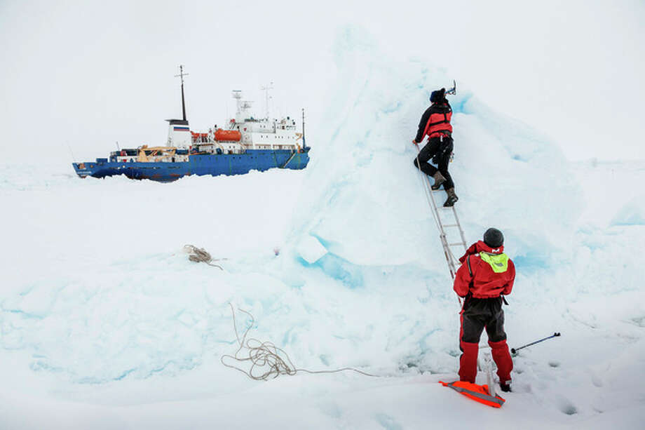 In this Tuesday, Dec. 31, 2013 image provided by Australasian Antarctic Expedition/Footloose Fotography, Ben Maddison and Ben Fisk from the Russian ship MV Akademik Shokalskiy work to place a wind indicator atop an ice feature near the trapped ship 1,500 nautical miles south of Hobart, Australia. Passengers on board a research ship that has been trapped in Antarctic ice for a week are expected to be rescued by helicopter, after three icebreakers failed to reach the paralyzed vessel, officials said Tuesday. (AP Photo/Australasian Antarctic Expedition/Footloose Fotography, Andrew Peacock) EDITORIAL USE ONLY / AustraAustralasian Antarctic Expedition/Footloose Fotography