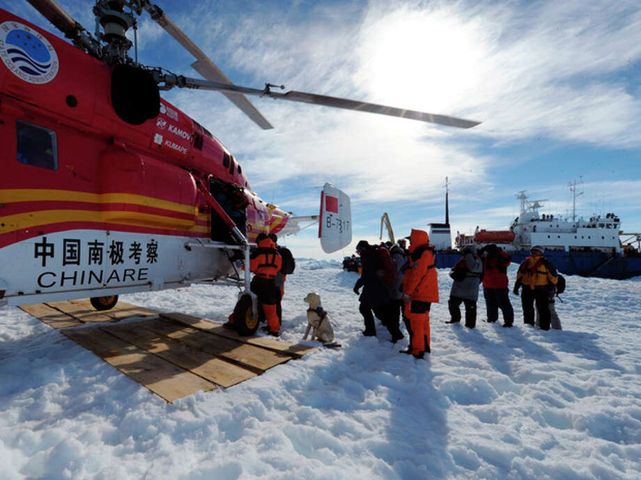 In this photo provided China's official Xinhnua News Agency, passengers from the trapped Russian vessel MV Akademik Shokalski, seen at right, prepare to board the Chinese helicopter Xueying 12 in the Antarctic Thursday, Jan. 2, 2014. A helicopter rescued all 52 passengers from the research ship that has been trapped in Antarctic ice, 1,500 nautical miles south of Hobart, Australia, since Christmas Eve after weather conditions finally cleared enough for the operation Thursday. (AP Photo/Xinhua, Zhang Jiansong) NO SALES / Xinhua
