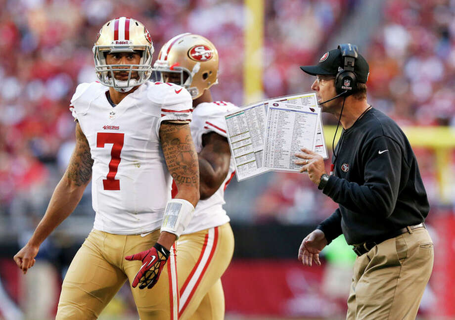 San Francisco 49ers head coach Jim Harbaugh, right, talks with quarterback Colin Kaepernick (7) prior to a play during the first half of an NFL football game against the Arizona Cardinals, Sunday, Dec. 29, 2013, in Glendale, Ariz. (AP Photo/Ross D. Franklin) / AP