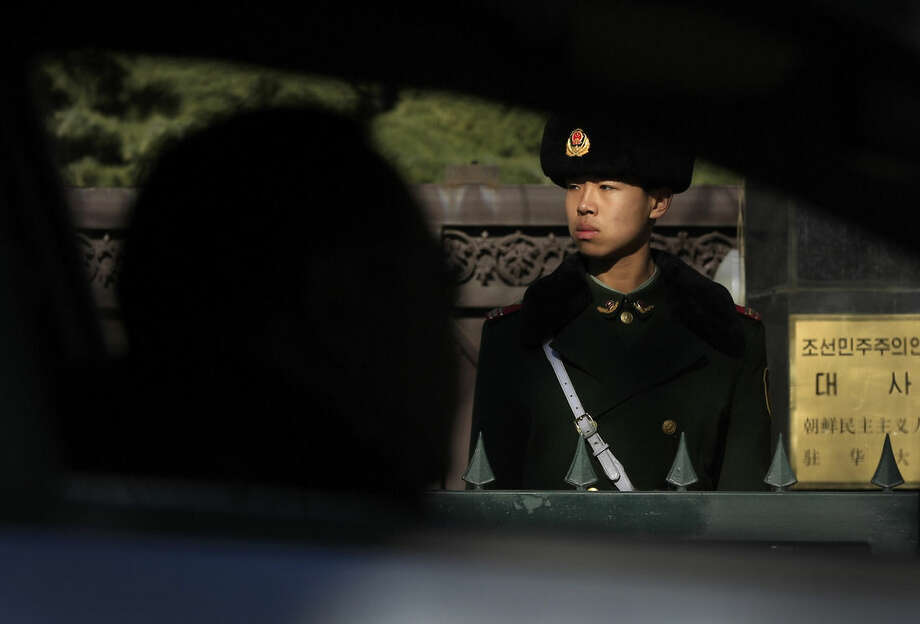 A driver is silhouetted as a Chinese paramilitary policeman stands guard outside the North Korean Embassy in Beijing, Wednesday, Jan. 6, 2016. North Korea said it conducted a powerful hydrogen bomb test Wednesday, a defiant and surprising move that, if confirmed, would be a huge jump in Pyongyang's quest to improve its still-limited nuclear arsenal. (AP Photo/Andy Wong)