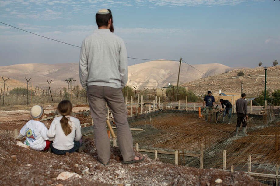 Jewish settler family members look at a construction of a new house at Gitit settlement in the West Bank's Jordan Valley, Thursday, Jan. 2, 2014. A senior Israeli Cabinet minister and more than a dozen hawkish legislators poured cement at a construction site in a settlement in the West Bank's Jordan Valley on Thursday, in what they said was a message to visiting U.S. Secretary of State John Kerry that Israel will never relinquish the strategic area. (AP Photo/Oded Balilty) / AP