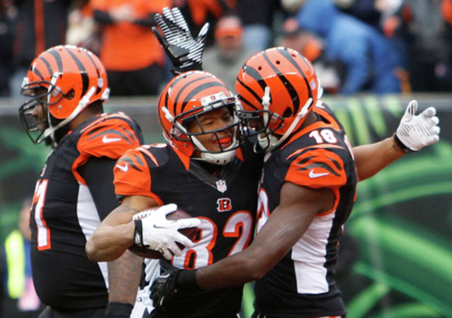 Cincinnati Bengals wide receiver A.J. Green (18) congratulates wide receiver Marvin Jones (82) after Jones caught a 16-yard touchdown pass in the first half of an NFL football game against the Baltimore Ravens, Sunday, Dec. 29, 2013, in Cincinnati. (AP Photo/David Kohl) / FR51830 AP