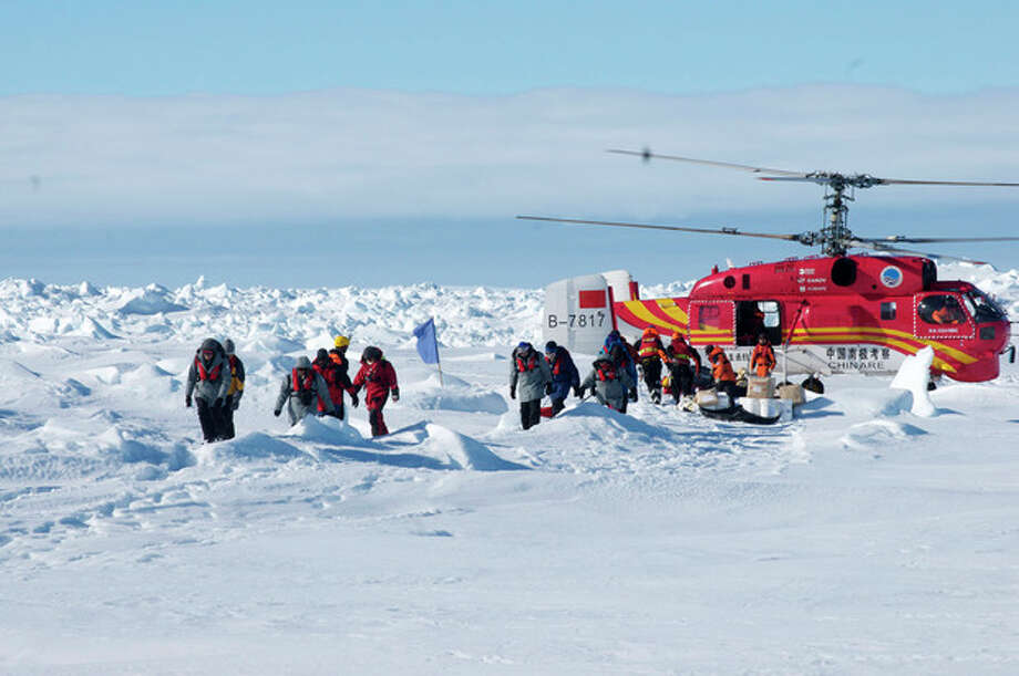 In this image provided by Australasian Antarctic Expedition, passengers trapped for more than a week on the icebound Russian research ship MV Akademik Shokalskiyin are rescued by a Chinese helicopter Thursday, Jan. 2, 2014. The helicopter rescued all 52 passengers from the research ship that has been trapped in Antarctic ice, 1,500 nautical miles south of Hobart, Australia, since Christmas Eve after weather conditions finally cleared enough for the operation Thursday. (AP Photo/Australasian Antarctic Expedition, Jessica Fitzpatrick) EDITORIAL USE ONLY, ONE TIME USE, NO ARCHIVES; NO SALES / Australasian Antarctic Expedition