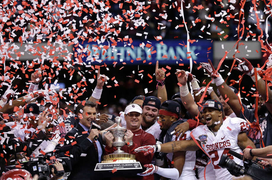 Oklahoma head coach Bob Stoops holds the Sugar Bowl trophy with his team after defeating Alabama 45-31 in the NCAA college football matchup in New Orleans, Thursday, Jan. 2, 2014. (AP Photo/Rusty Costanza) / FR170655 AP