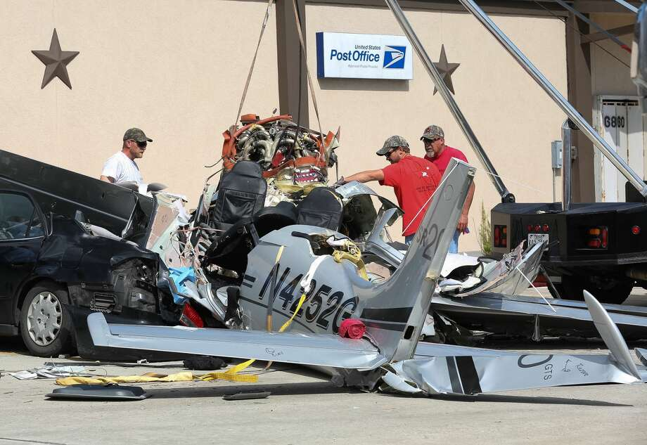 On Friday, June 10, 2016, a crew works to remove the wreckage of a small plane from a parking lot where it crashed Thursday killing three people, in Houston. Photo: Jon Shapley / Houston Chronicle